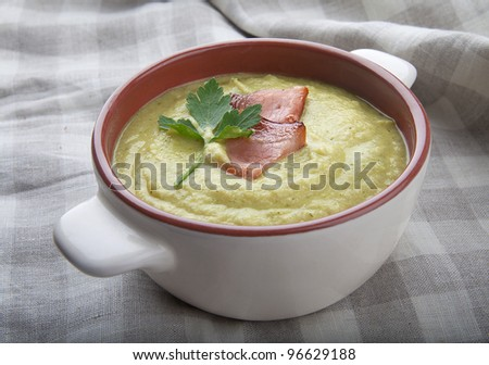 Cream soup in the bowl with bacon and parsley
