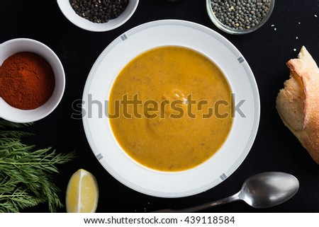 Cream soup of assorted lentil. Yellow and green lens, spices as raw for meal and lemon on black background. Healthy, appetizing, delicious, vegetarian food. Top view, copy space. - stock photo