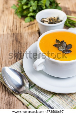 cream soup of pumpkin and vegetables in white plate on wooden table