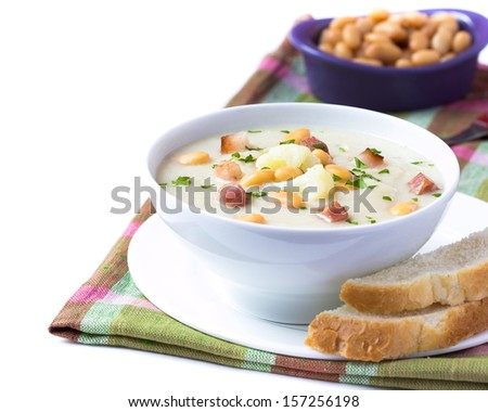 Cream soup with cauliflower, white beans and fried bacon in white bowl ...
