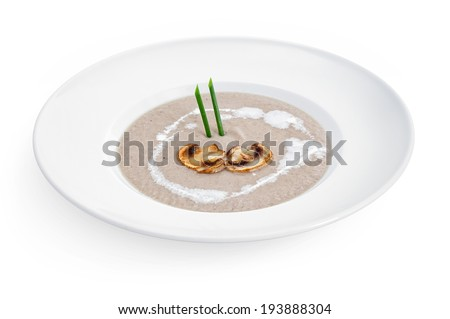 Cream soup with white mushrooms on the plate, isolated on white background - stock photo