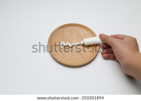 Cream squeezed out from tube on plate - stock photo