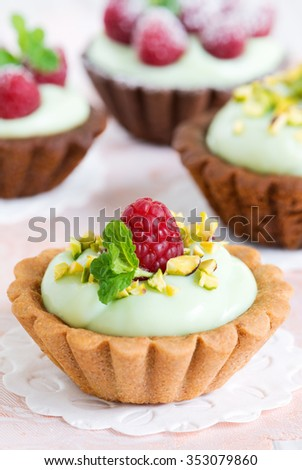 Cream tarts with pistachio nuts, raspberry and peppermint