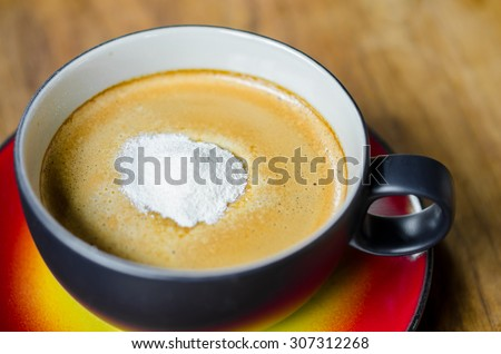 Creamer on a cup of coffee on wooden background. - stock photo