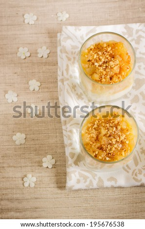 creamy dessert with caramelized pears and nuts in the glass. toning. selective focus on pear in  top glass - stock photo