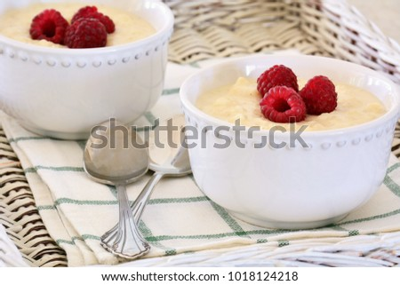 Creamy home made rice pudding with sweet juicy raspberries on wicker tray