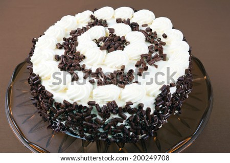 Creamy layer cake with chocolate shavings in the brown style - stock photo