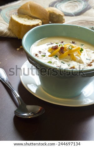 Creamy loaded baked potato soup with scallion garnished and fresh Italian bread