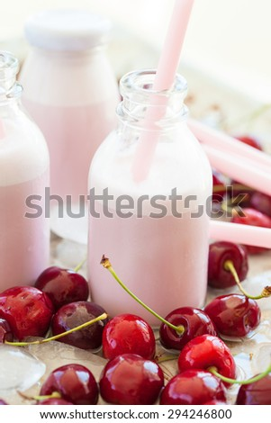 Creamy milk shake with fresh cherries on cold ice cubes