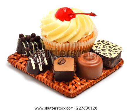 Creamy muffin with chocolate sweets, candies isolated on white background - stock photo