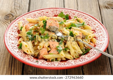 Creamy pasta with salmon and parsley in red plate - stock photo
