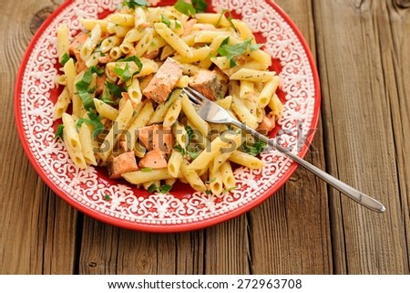 Creamy pasta with salmon and parsley in red plate, copyspace - stock photo