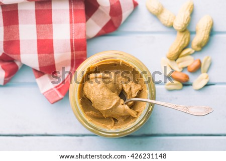 Creamy peanut butter and peanuts. Spreads peanut butter in the jar. - stock photo