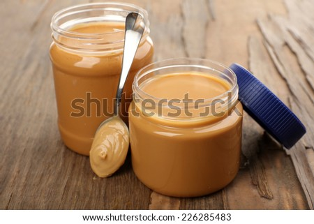 Creamy peanut butter in jar, on wooden table