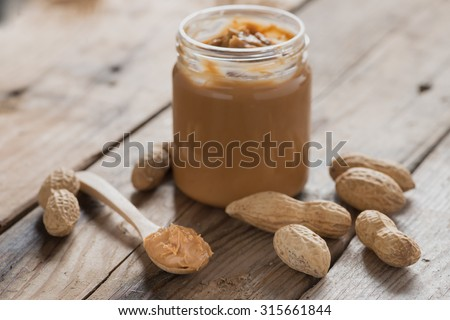 Creamy peanut butter on wood table. Selective focus. - stock photo