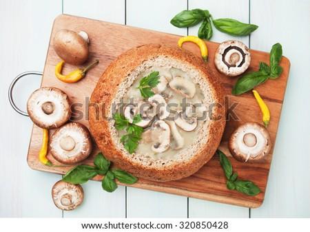 Creamy portabello mushroom soup served in wholegrain bread - stock photo