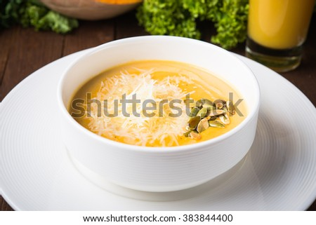 Creamy pumpkin soup with sids and parmesan on dark wooden background close up. - stock photo