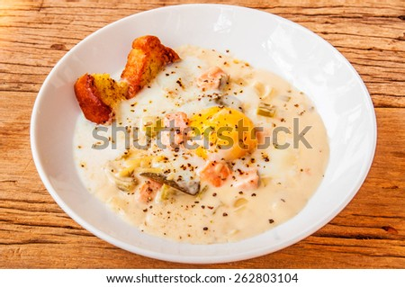 Creamy Salmon soup with Egg Yolk and Garlic Bread Baked. Concept and Idea of Homemade Cooking Fusion Food Cuisine. On wood table background and textured. - stock photo