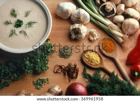 Creamy soup surrounded by ingredients on a butcher block surface - stock photo