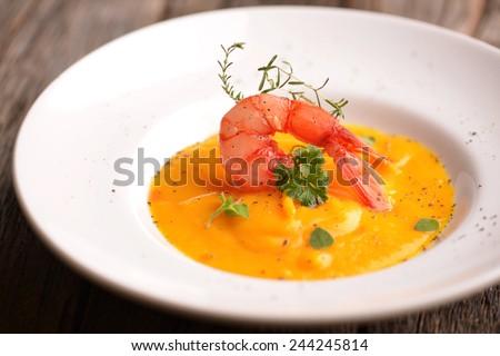 Creamy soup with and tiger prawns  - stock photo
