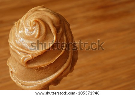 Creamy swirls of peanut butter with color coordinated wood cutting board in background.  Macro with extremely shallow dof. - stock photo
