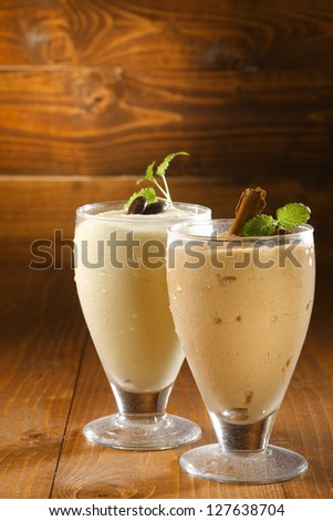 Creamy thick milkshakes or pudding dessert in chilled glasses garnished with chocolate and served on a wooden background with copyspace - stock photo