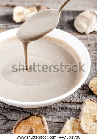 Creamy vegan mushroom soup with champignon and shiitake in white bowl. Soup drains from spoon into bowl. Wood background. Dry shiitake on front. - stock photo