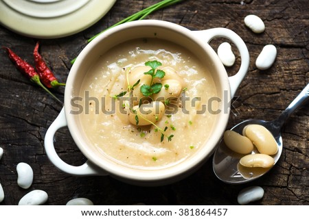 Creamy white bean soup on wooden background