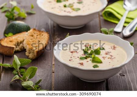 Creamy zucchini soup with chilli and oregano, crispy bread with garlic - stock photo