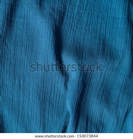Creased blue cloth material fragment as a background texture - stock photo