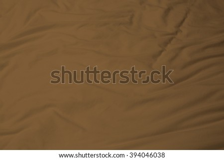 creased brown cloth material fragment as a background. - stock photo