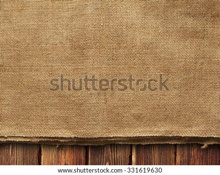 Creased fabric on wooden wall background - stock photo