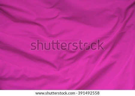 Creased pink cloth material fragment as a background. - stock photo