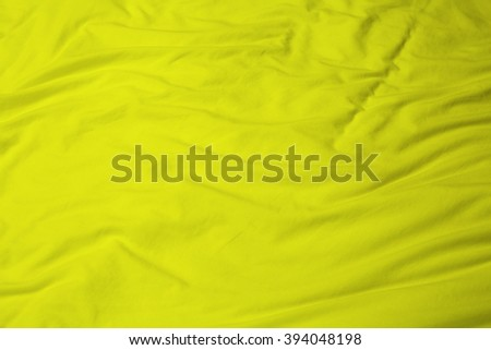 creased yellow cloth material fragment as a background. - stock photo