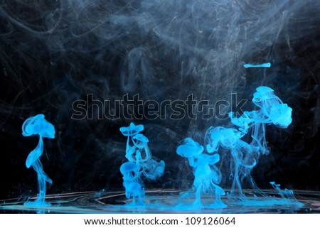 Creating blue in smoke Description: Blue ink in the water - stock photo