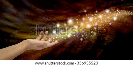 Creating Magic - Female open hand appearing to send out a stream of sparkles and glitter on a golden and black flowing background - stock photo