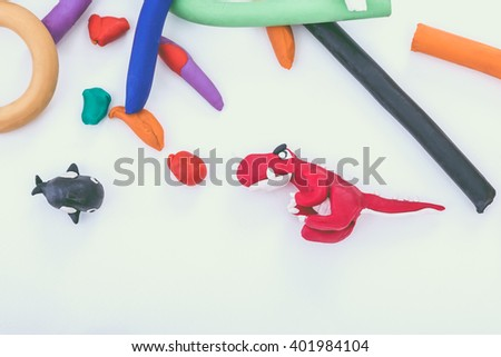 Creating red dinosaur and whale clay model, on white background. Animals from play dough. Education concept. - stock photo