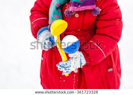 Creating snowball at winter time, snow background. Kids time fun. - stock photo