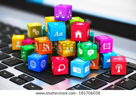 Creative abstract computer media and internet communication business concept: macro view of heap of colorful cubes with application icons and symbols on laptop keyboard with selective focus effect - stock photo