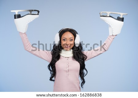 Creative African girl having skates instead of hands. Looking funny and isolated on blue  - stock photo