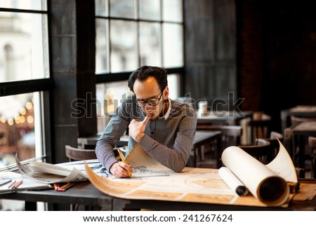 Creative architect projecting with pencil on the big drawings in the dark loft office or cafe - stock photo