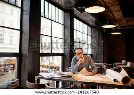 Creative architect thinking on the big drawings in the dark loft office or cafe. General plan with windows - stock photo