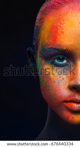 Creative art make up, half of female face. Holi colors. Closeup cropped studio portrait of young fashion model with bright colorful mix of paint on her face on black background