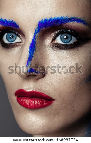 Creative art makeup of a young girl with blue eyes. Strokes of paint on his face and hair