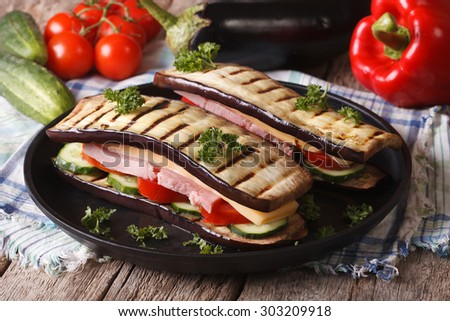 Creative aubergine sandwich with fresh vegetables, ham and cheese close-up on a plate.
