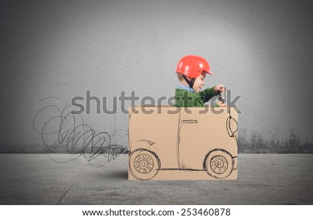 Creative baby plays with his cardboard car - stock photo