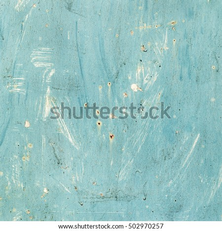 Creative background of rusty metal, painted blue paint carelessly with the remnants of torn paper. Grungy metal surface. Great background or texture for your project.