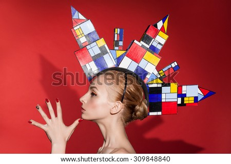 Creative beauty fashion glamour portrait of young caucasian woman with great hat like a town on her head. Colorful image, studio shot. - stock photo