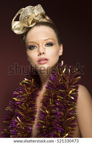 creative beauty portrait of stunning blonde female with ribbon in the hair-style, sparkly tinsel on nude shoulders and glitter golden make-up. Red backround