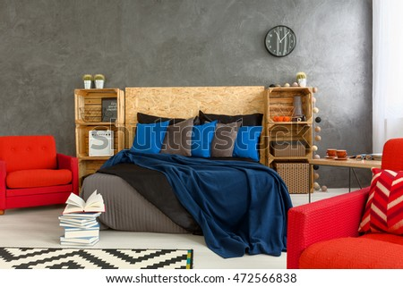 Creative bedroom with double bed and red armchairs